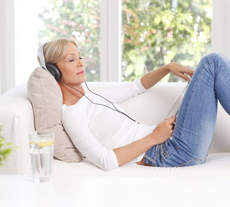 woman listening to podcast to unwind